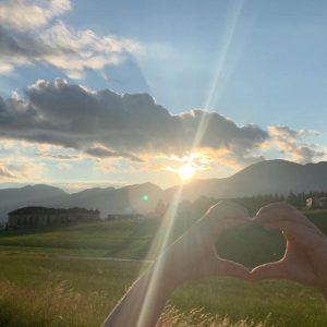 Hände formen Herz im Sonnenschein